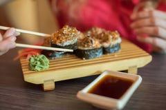 女孩吃日本食物保留与木chopsti的寿司卷 免版税图库摄影