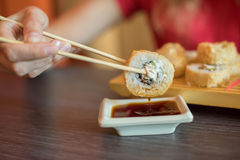 女孩吃日本食物保留与木chopsti的寿司卷 库存图片