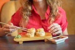 女孩吃日本食物保留与木chopsti的寿司卷 免版税库存图片