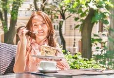 女孩吃着一个点心(蛋糕)在café 免版税库存图片