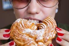 女孩吃着乳蛋糕圆环-一个传统俄国点心 免版税库存照片