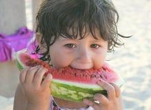 女孩吃西瓜的3年 免版税库存照片