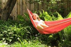 女孩吊床躺下 免版税库存图片