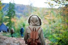 女孩后面在秋天森林里 库存照片