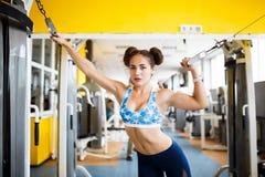 女孩向在健身房的体育求助 女孩向在健身房的体育求助 一种健康生活方式的概念 免版税库存照片