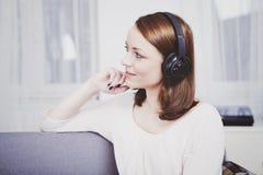 女孩听到与耳机的音乐 库存图片