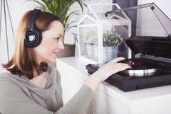 女孩听到与耳机的音乐 免版税图库摄影