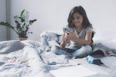 女孩听到她在一个灰色智能手机的喜爱的音乐在一个对耳机和微笑帮助下 库存照片
