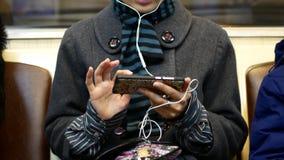 女孩听到音乐或观看在一个智能手机的录影在地铁 影视素材