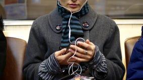 女孩听到音乐或观看在一个智能手机的录影在地铁 股票录像