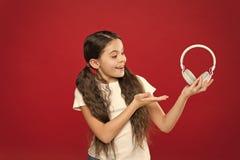 女孩听在红色背景的音乐耳机 现代小配件概念 音乐口味 音乐播放一个重要部分生活 库存照片