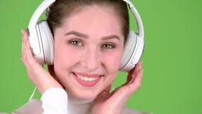 女孩听在耳机的旋律美妙歌曲 绿色屏幕 关闭 慢的行动 股票视频