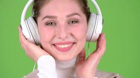 女孩听在耳机的旋律美妙歌曲 绿色屏幕 关闭 影视素材