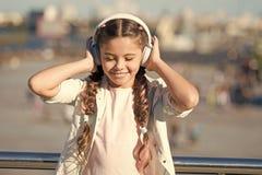 女孩听的音乐享受喜爱的歌曲 女孩有耳机都市背景 音乐的正面影响 库存图片