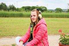 女孩听的音乐外面 免版税图库摄影