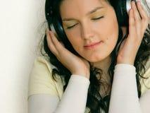 女孩听的音乐年轻人 库存图片