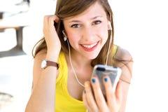 女孩听的MP3播放器tp 免版税库存照片