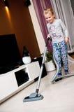 女孩吸尘的室 免版税库存图片