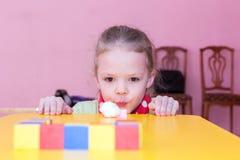女孩吹棉花球入目标 免版税库存图片