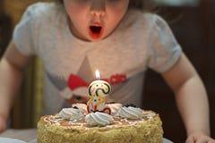 女孩吹灭在生日蛋糕的一个蜡烛 图库摄影