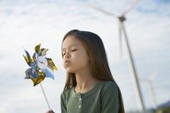 女孩吹的玩具风车 免版税库存图片