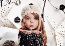 女孩吹的白色圣诞节雪花在演播室 免版税库存图片