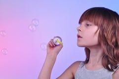 女孩吹的肥皂泡 免版税库存图片
