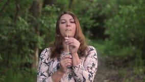 女孩吹的蒲公英在森林和美丽微笑里 慢的行动 HD 股票视频