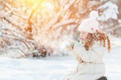 女孩吹的雪用她的手,在晴朗的冬天步行 免版税库存照片