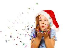 女孩吹从棕榈的五彩纸屑在圣诞老人帽子 库存图片