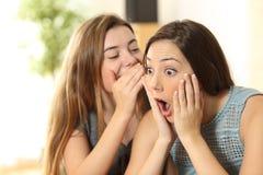 女孩告诉秘密对她的惊奇朋友 库存图片