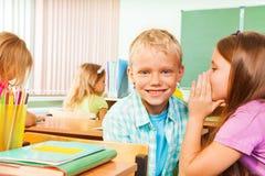 女孩告诉秘密对微笑的男孩在教室 免版税图库摄影