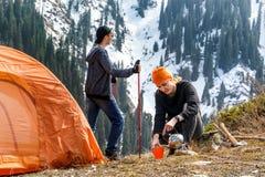 女孩和一个人中止的用旅游帐篷饮用的茶或咖啡在森林积雪覆盖的山背景  遇见的走 免版税库存照片