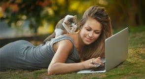 女孩和一只猫在草观看的膝上型计算机 免版税库存照片