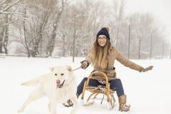 女孩和一条狗在雪 库存图片