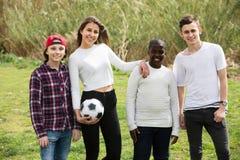 女孩和三个男孩在春天公园和微笑的踢橄榄球 库存图片