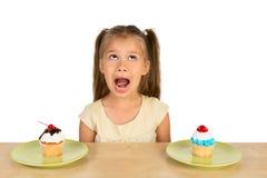 女孩和两块杯形蛋糕 图库摄影