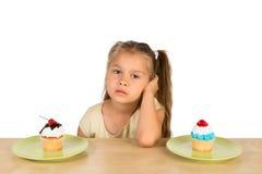 女孩和两块杯形蛋糕 库存图片