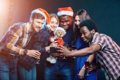 女孩和人做selfie的圣诞老人帽子的在党 圣诞节,新年概念 库存照片