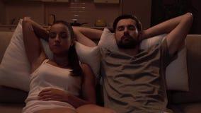 女孩和人坐沙发并且睡觉 他们非常深的呼吸 夫妇握他们的在头后的手 在移动的照相机紧密 股票视频