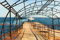 女孩和人看看水,站立在老码头和等待一艘适当的船 免版税库存照片