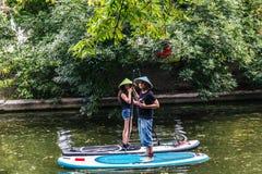 女孩和人站立在冲浪板的草帽的 免版税库存照片