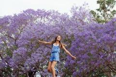 女孩和兰花楹属植物树 免版税库存图片
