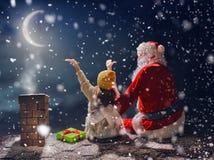 女孩和圣诞老人坐屋顶 库存图片