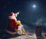 女孩和圣诞老人坐屋顶 库存照片