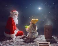 女孩和圣诞老人坐屋顶 免版税库存图片