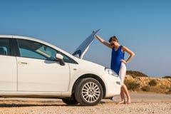 女孩和她残破的白色汽车 库存照片