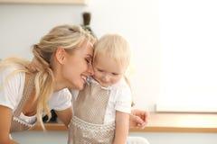 女孩和她白肤金发的妈妈笑米黄的围裙的使用和,当揉面团在厨房里时 自创酥皮点心 库存照片