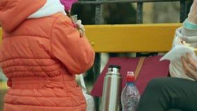 女孩和她的妈妈坐公园长椅并且吃着一个可口点心并且喝从热水瓶的茶 库存照片