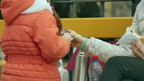 女孩和她的妈妈坐公园长椅并且吃着一个可口点心并且喝从热水瓶的茶 免版税库存图片